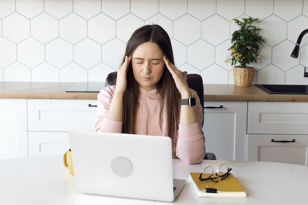 Een vrouw heeft hoofdpijn van het werken op een computer