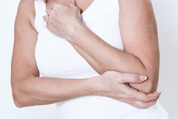 Een vrouw heeft pijn in haar arm. ze hield zich eraan.