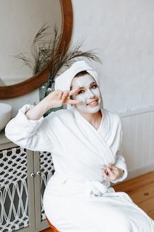 Een vrouw heeft plezier en maakt gezichten in de badkamer met een kleimasker op haar gezicht