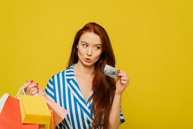 Een vrouw heeft verschillende gekleurde tassen met verschillende aankopen in haar handen met een creditcard