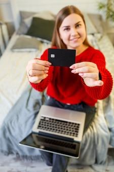 Een vrouw houdt een creditcard in haar handen, klaar om te winkelen, draagt een rode trui, zit thuis op bed, een bankcliënt toont haar creditcard. online winkelen vanuit huis. selectieve focus