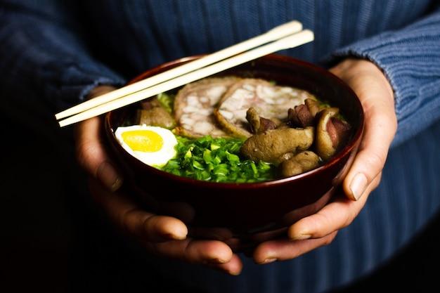 Een vrouw houdt een donkere kom vast met een aziatisch gerecht bestrooid met vers gehakte uien.