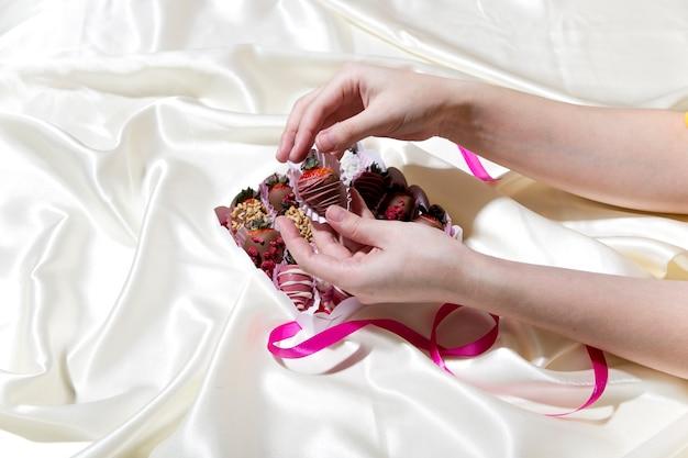 Een vrouw houdt een doos met chocolade omhulde aardbeien vast