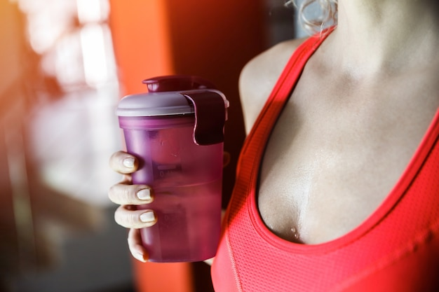 Een vrouw houdt een fles waterclose-up.