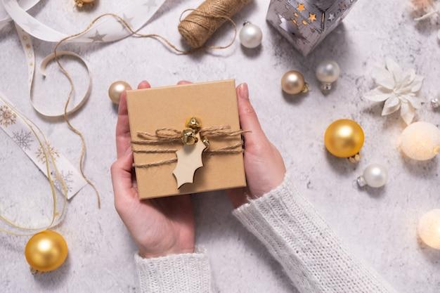 Een vrouw houdt een geschenkdoos vast die is versierd met touw en een houten label ter voorbereiding op kerstmis en nieuwjaar