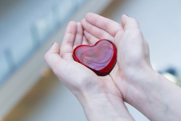 Een vrouw houdt een glazen rood hart in haar handen voor valentijnsdag of doneer hulp, liefde, warmte, zorg