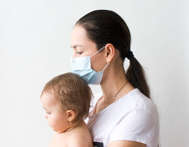 Een vrouw houdt een klein kind, moeder en kind op een witte achtergrond, close-up. kinderdag, moederdag