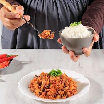 Een vrouw houdt een kom witte rijst met pittige geraspte tonijn vast, concept daily asian (koreaans japan thailand) menu. geselecteerde focus