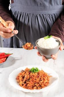 Een vrouw houdt een kom witte rijst met pittige geraspte vis vast, concept daily asian (koreaans japan thailand) menu