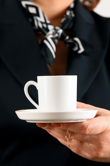 Een vrouw houdt een kopje gevuld met zwarte koffie of thee