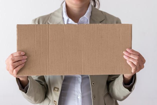 Een vrouw houdt een leeg bord voor haar gezicht