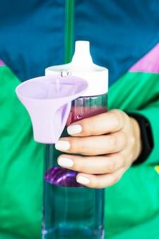 Een vrouw houdt een paarse waterfles in haar hand voor sporten