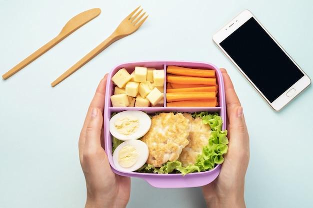 Een vrouw houdt een plastic lunchbox in haar handen. mobiele telefoon en bestek liggen op een blauwe achtergrond