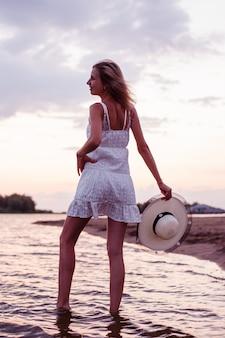 Een vrouw houdt een strohoed in haar handen, een mooie gelukkige blonde in een witte zomerjurk houdt de he...
