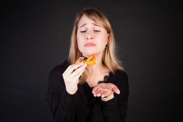 Een vrouw houdt een stuk pizza in haar handen en kijkt er vragend naar.