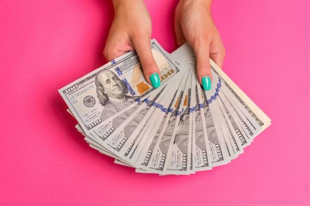 Een vrouw houdt geld in haar handen roze achtergrond bovenaanzicht kopieerruimte