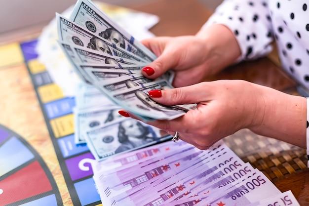 Een vrouw houdt in haar handen een bundel dollars en euro's gewonnen in een bordspel en training van zakelijke vaardigheden en strategieën op een speelse manier