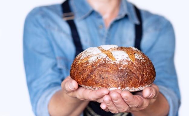 Een vrouw houdt in haar handen een smakelijk, knapperig, zelfgemaakt zuurdesembrood van rogge