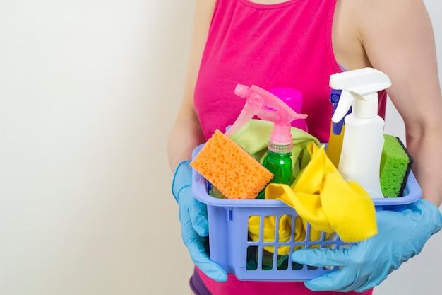 Een vrouw houdt reinigingsmiddelen om te wassen. ruimte kopiëren.