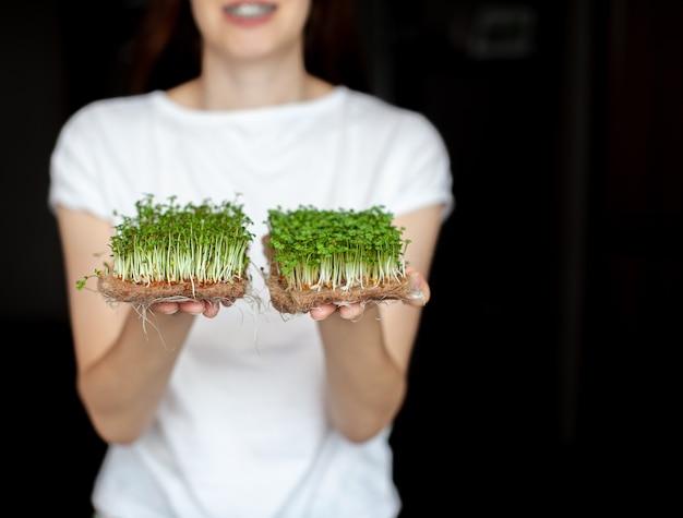 Een vrouw houdt thuis gekweekte microgroenten in haar handen microgroenten