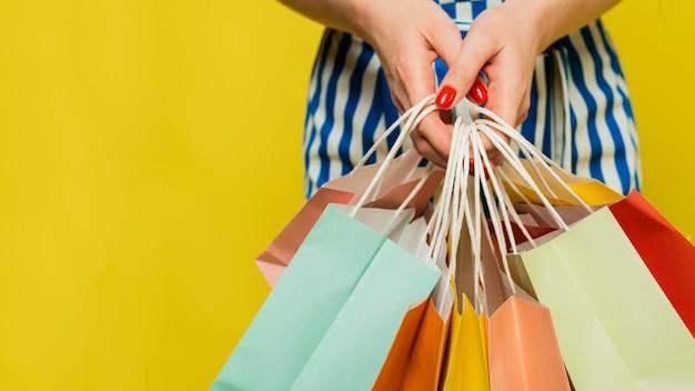 Een vrouw houdt verschillende gekleurde tassen met boodschappen verschillende aankopen in haar handen. het concept van winkelen en verkoop. webbanner.