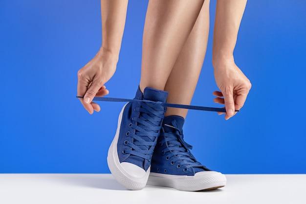 Een vrouw in blauwe gymschoenen knoopt haar schoenveters vast