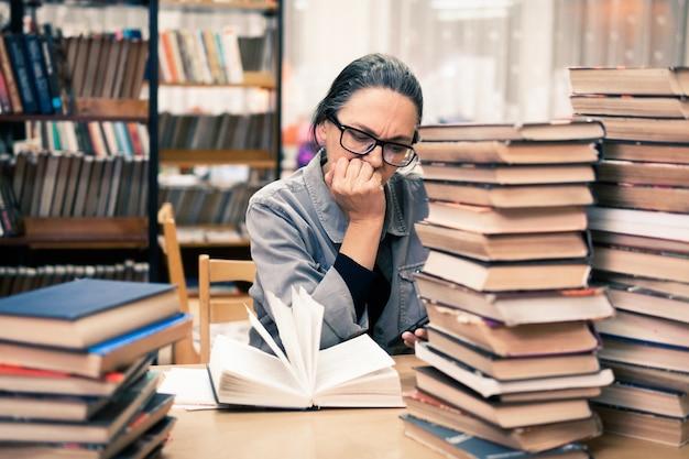 Een vrouw in de bibliotheek op zoek naar een boek. een vrouw van middelbare leeftijd kijkt naar een boek op de boekenplanken. ze bestudeert nieuwe richtingen en methoden.