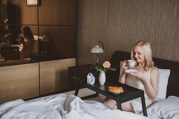 Een vrouw in de kamer drinkt koffie zittend in bed