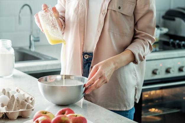 Een vrouw in de keuken voegt opgeklopte dooiers toe aan de opgeklopte eiwitten met een mixer voor het maken van appeltaart. koken.