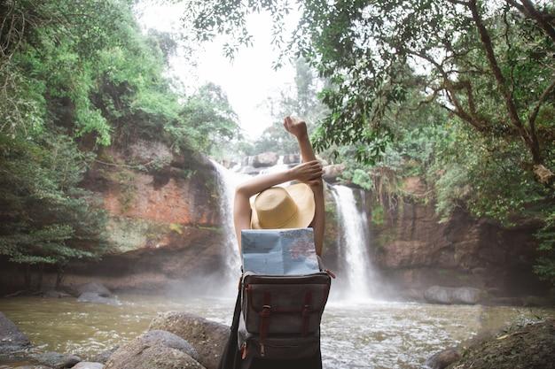 Een vrouw in de rivier met haar verhoogde handen naar waterval.