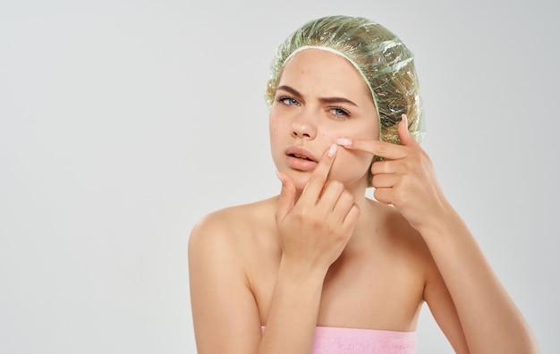Een vrouw in een badmuts perst puistjes op haar gezicht en een roze handdoek