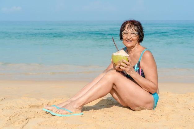 Een vrouw in een badpak met een kokosnoot kijkt naar de camera en lacht