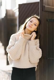 Een vrouw in een beige trui. een meisje in een lente- of herfststad. dame bij de houten poort.
