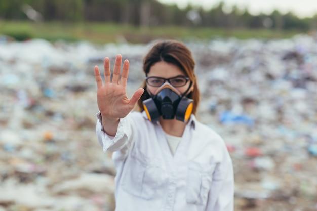 Een vrouw in een beschermd ademhalingspak op stortplaatsen, hand in hand, probeert de vervuiling van de planeet te stoppen, toont een stopbord met haar handen