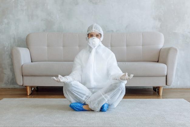 Een vrouw in een beschermend pak voor het desinfecteren van huishoudelijke artikelen en meubels zit te mediteren in een kamer. home desinfectie