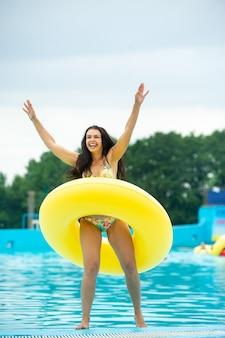 Een vrouw in een bikini met een rubberen opblaasbare cirkel die in de zomer speelt en zich vermaakt in het zwembad van het pretpark.