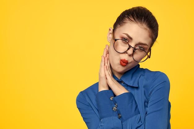 Een vrouw in een blauw shirt en bril met lichte make-up op haar gezicht gebaart met haar handen op een gele ruimte copy space.