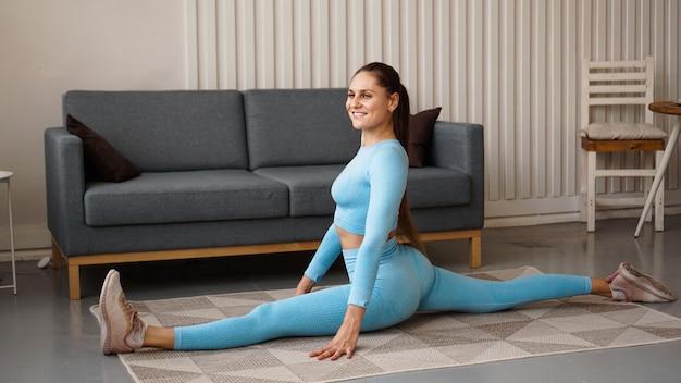 Een vrouw in een blauw trainingspak zit aan een touw. thuistraining tijdens quarantaine. zelfstudie fitness en stretching