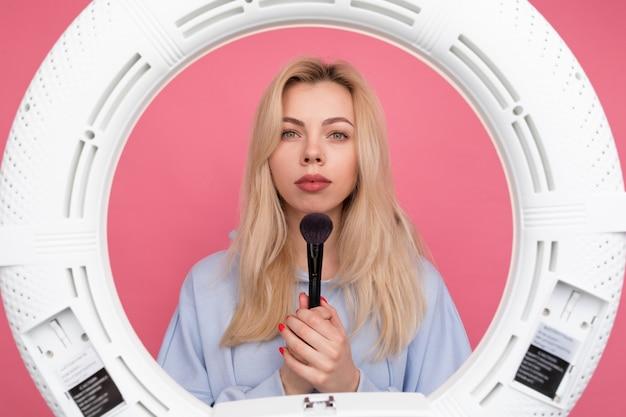 Een vrouw in een blauwe hoodie doet haar make-up met een borstel voor een ringlamp