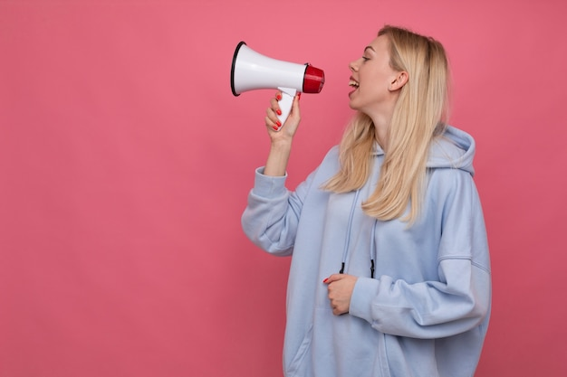 Een vrouw in een blauwe hoodie schreeuwt in een luidspreker