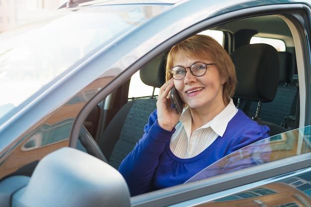 Een vrouw in een blauwe jas die in een auto door de stad rijdt