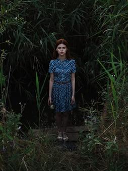 Een vrouw in een blauwe jurk in de avond in de buurt van het groene gras op het bovenaanzicht van de natuur