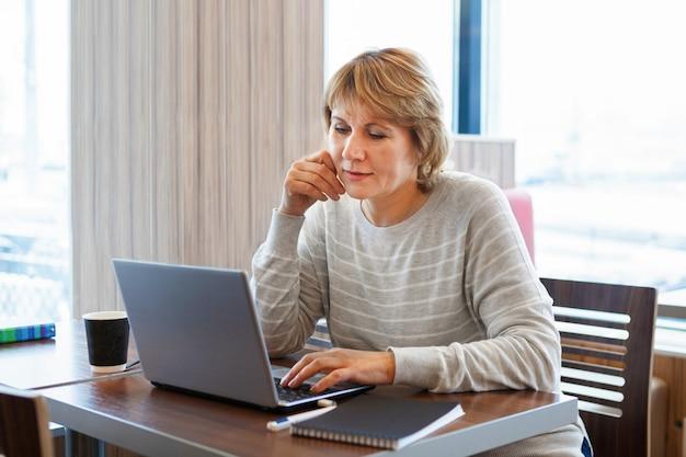 Een vrouw in een café die op een laptop werkt. het concept van zaken en werken op afstand.