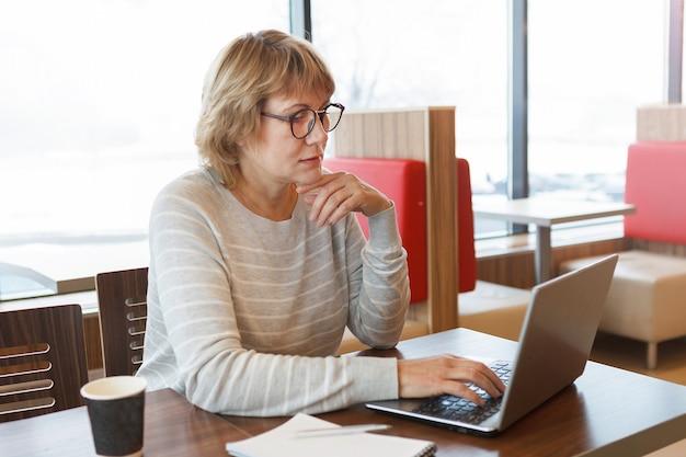 Een vrouw in een café werkt op een laptop. ze lacht. een vrouw van middelbare leeftijd, een volwassene in een kantoor. ze kijkt naar sociale media.