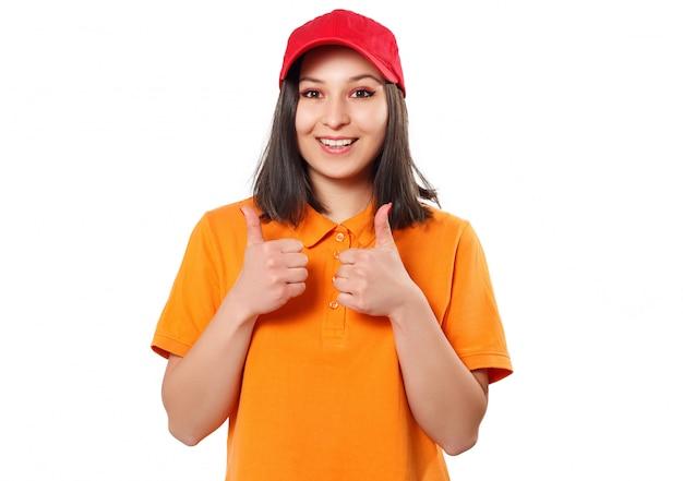 Een vrouw in een fel poloshirt en een rode baseballpet toont een duim omhoog