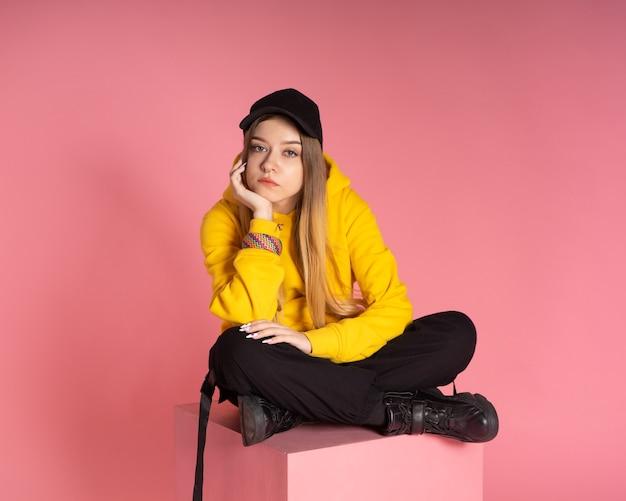 Een vrouw in een gele hoodie, een zwarte pet met een doorboorde neus, een brede armband in de kleuren van de lgbtq-regenboog