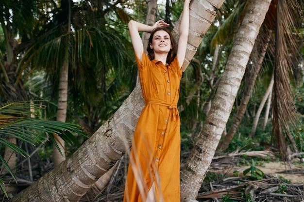 Een vrouw in een gele jurk en hoed loopt langs de oceaan langs het zand met palmbomen