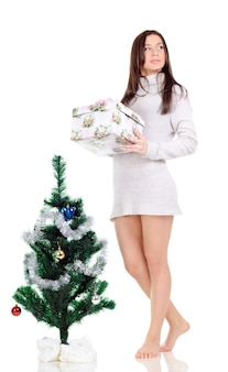 Een vrouw in een grijze jurk poseert bij een kerstboom met een cadeautje in haar handen en kijkt weg