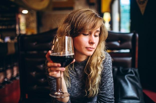 Een vrouw in een grijze top zit alleen in een restaurant met een glas wijn. romantisch meisje met blonde krullen, ontspannen in een cafe en verlegen glimlach, naar beneden te kijken.