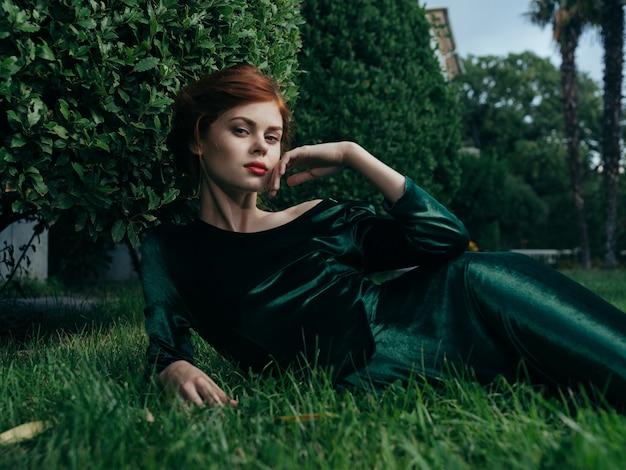 Een vrouw in een groene jurk in de open lucht ligt op het gras exotische decoratie carnaval